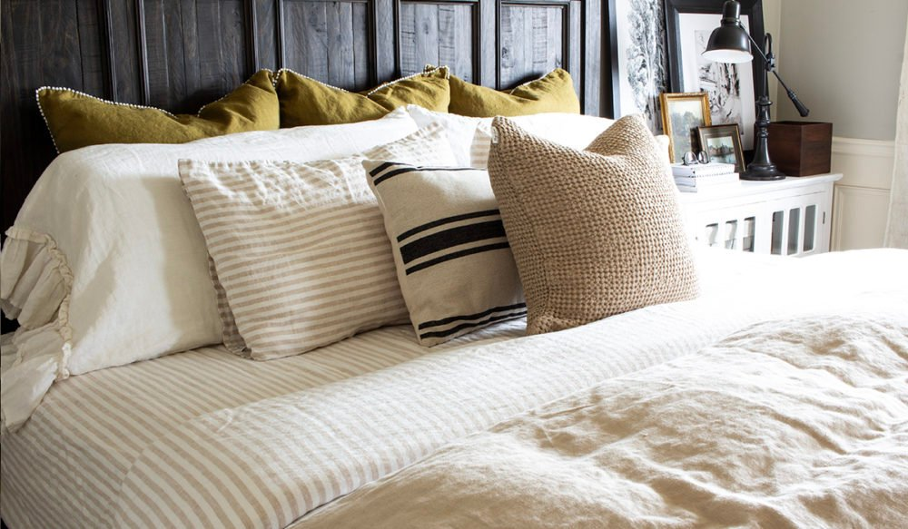 olive green euro pillows behind ruffled linen pillows and striped natural linen pillows