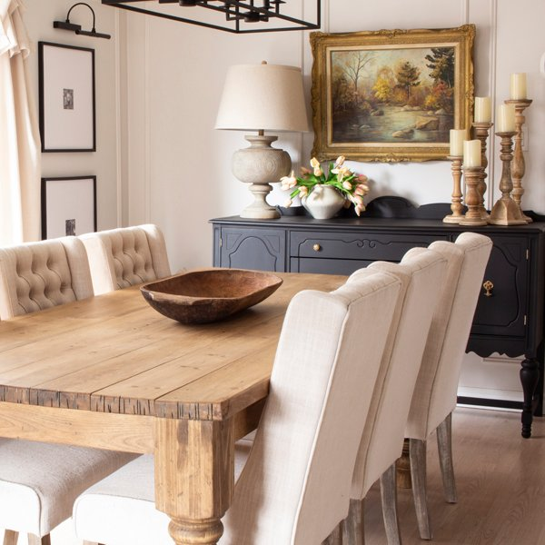 neutral dining room with black buffet and farmhouse table