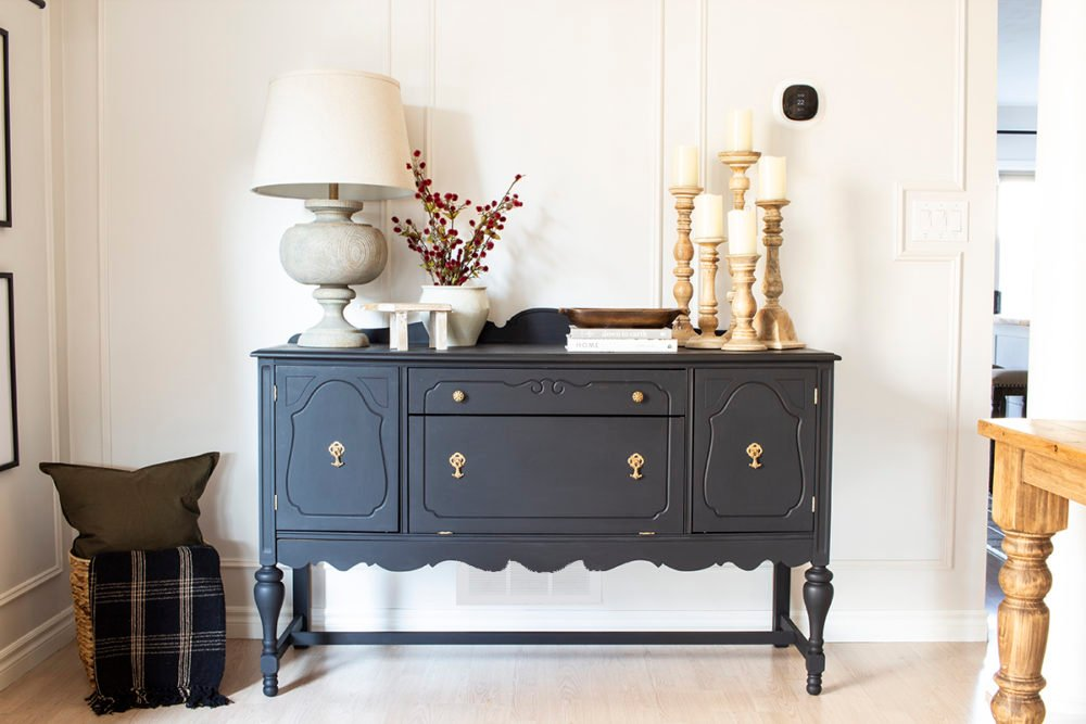 black painted buffet sideboard in dining room with lamp and candlesticks