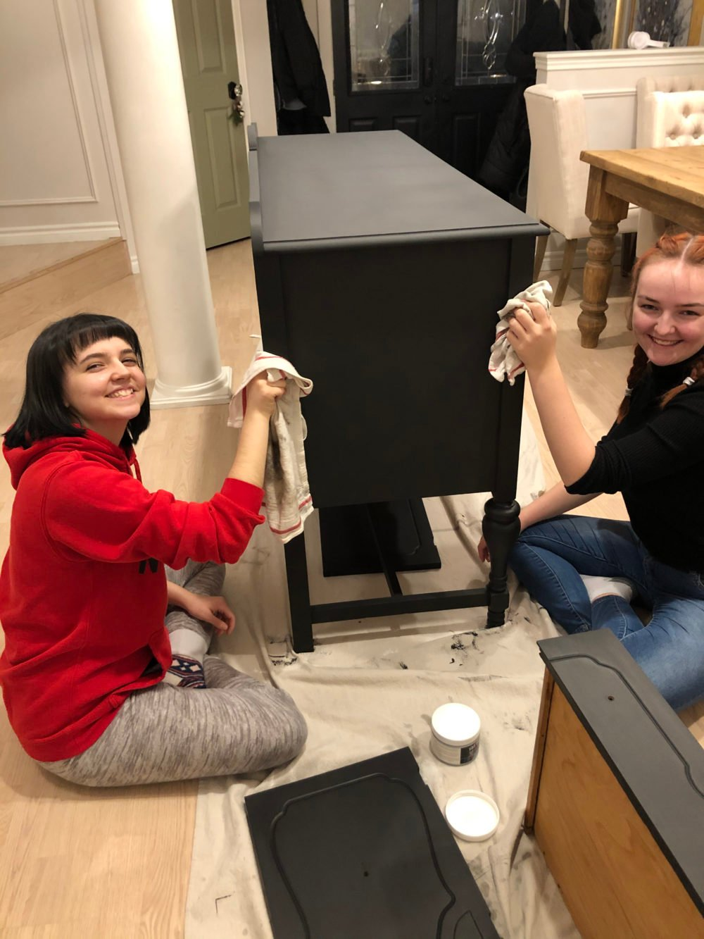 girls waxing over black paint with clear wax and old rags