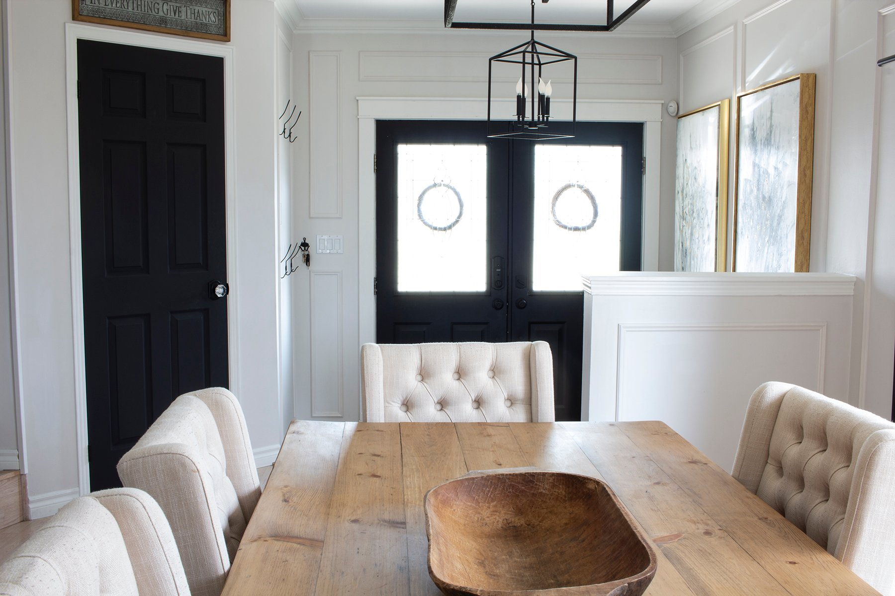 dining room with wood farmhouse table towards entry with double black doors