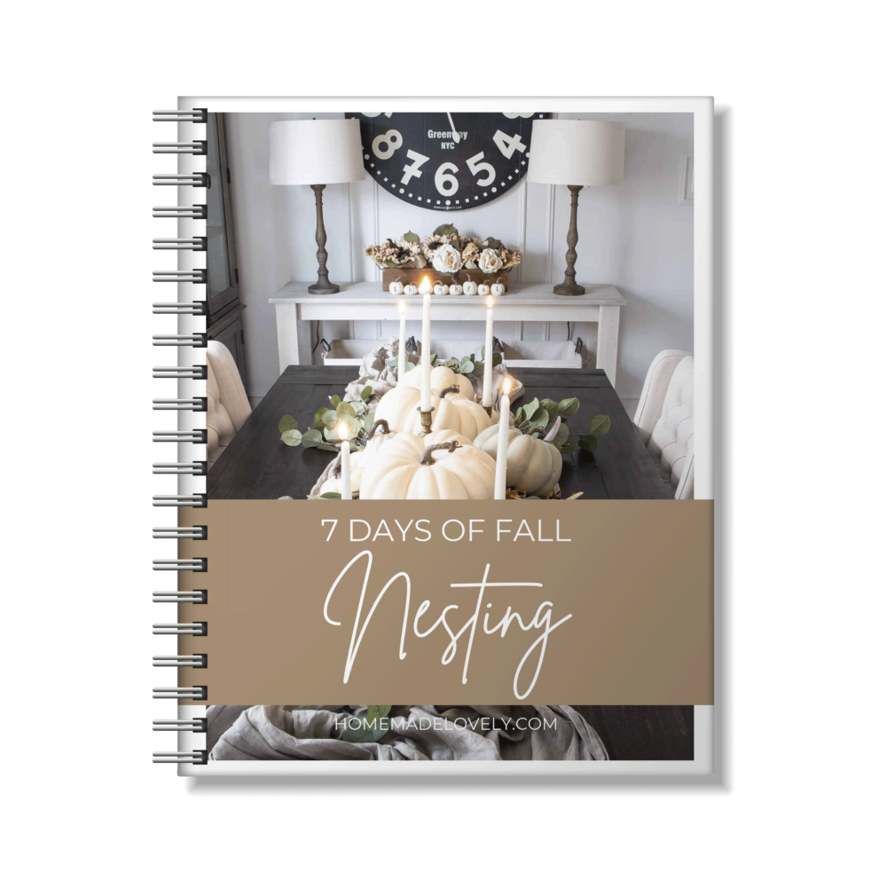 7 days of fall nesting text over a beige rectangle over image of white pumpkins on table