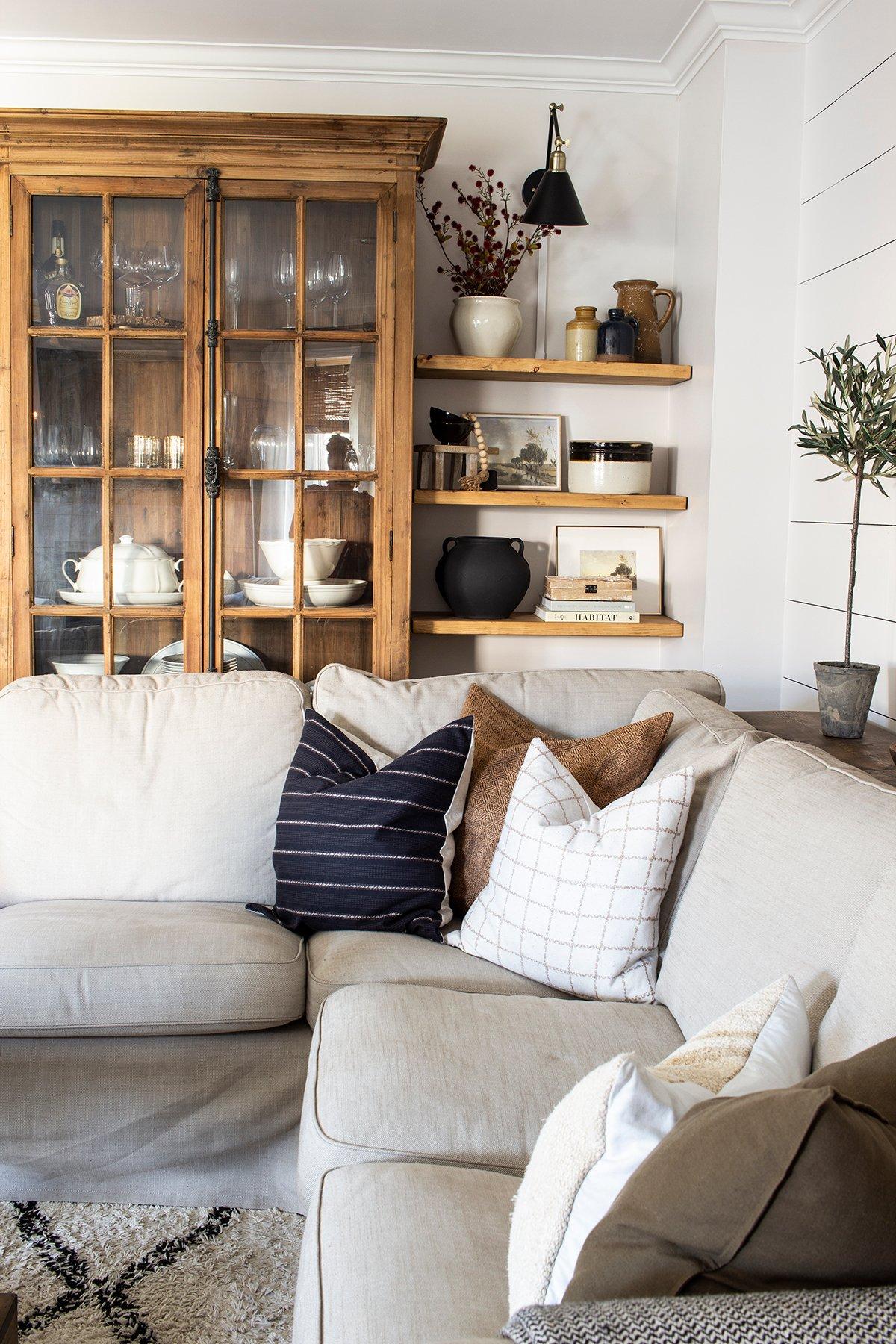 beige sofa coordinated pillows shiplap wall open shelves