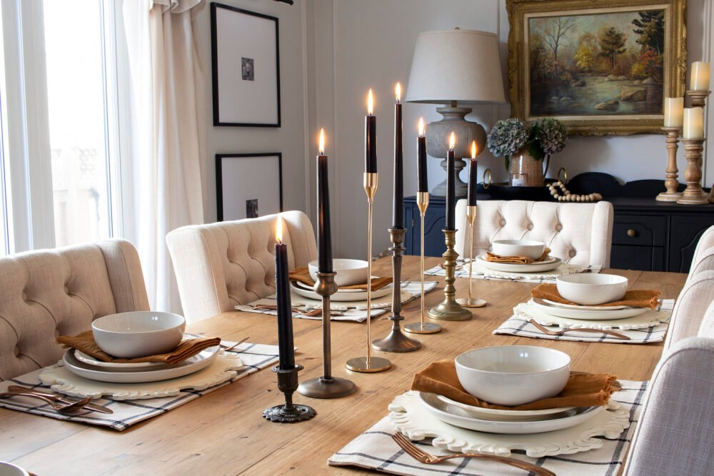 brass candlesticks and black taper candles on rustic table