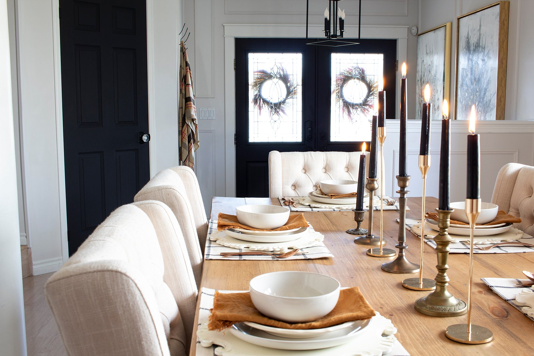 fall dining table with brass candlesticks black doors in background