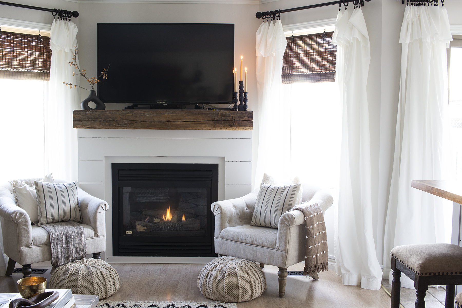 white shiplap and barn beam fireplace tve above two windows
